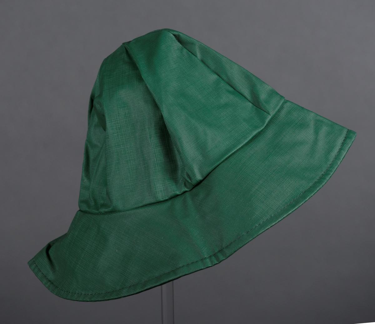 """En grønn regnhatt laget av bomullsstoff med PVC-belegg. Hodeplaggets pull er sveiset sammen av 6 deler. Bremmen er like bred hele veien rundt. Ytterst på bremmen er det en maskinsydd kant. Regnhatten er ikke foret. Langs kanten innvendig er det sydd på et kantebånd av bomull. Bak i hatten er det en merkelapp med identisk informasjon på begge sider, de """"Påført tekst/merker""""."""
