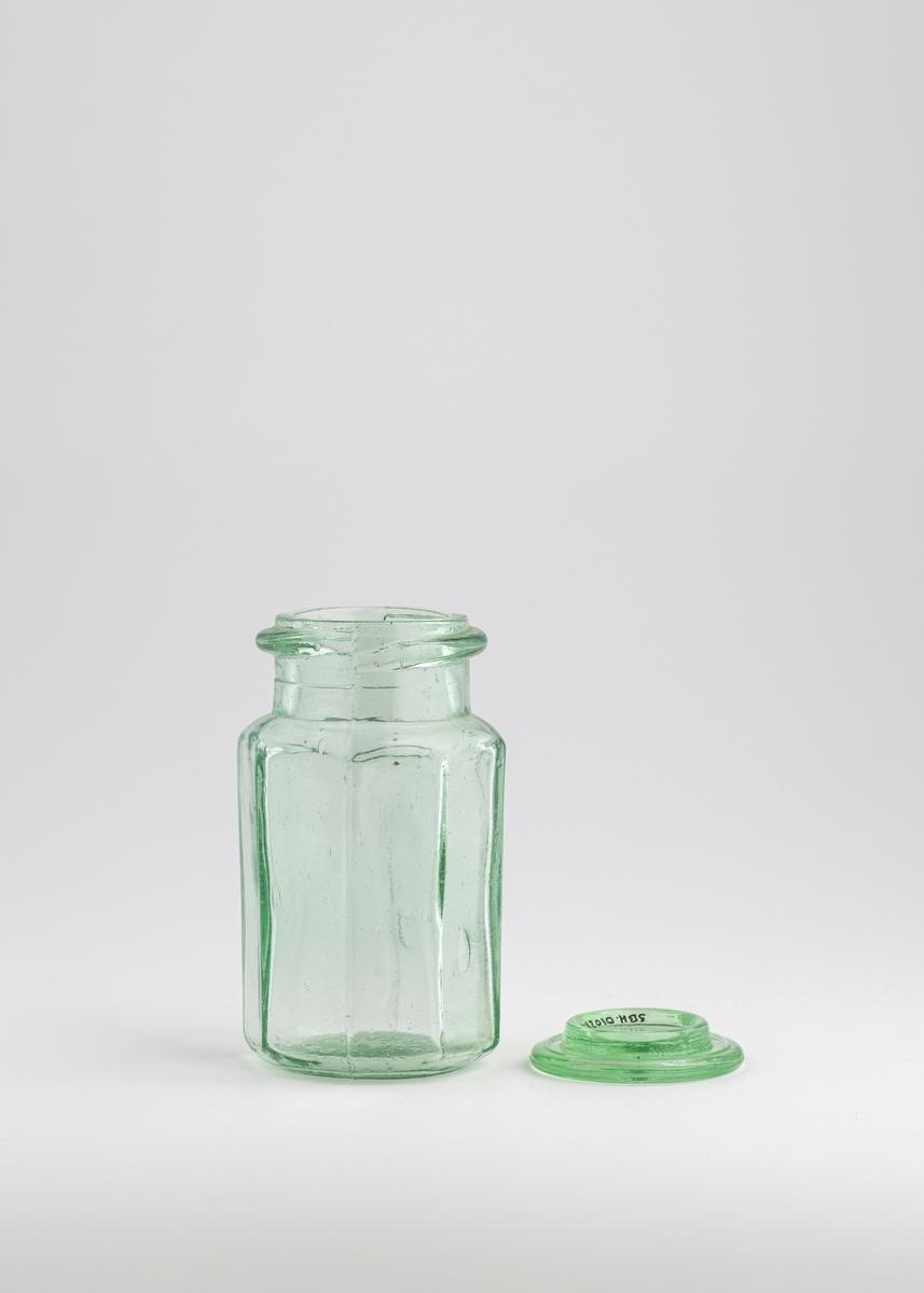 Åttekantet glass med rund åpning, høy kant og randt rundt toppen. Rundt glasslokk som ligger løst oppå.