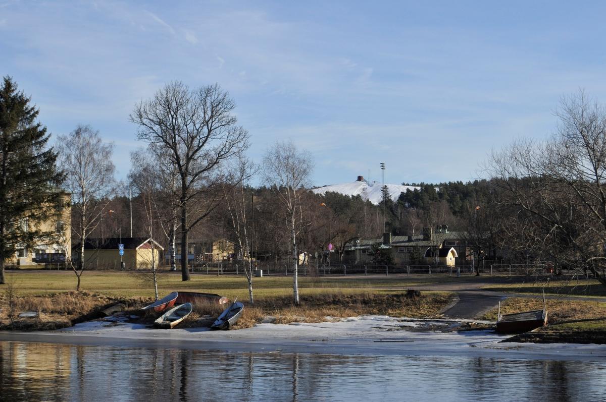 Arbogaåns södra strand med utsikt mot Kungsörsvägen och Teknikbackens snöklädda topp. Båtar ligger på isen. Gäddgårdsskolan till vänster.