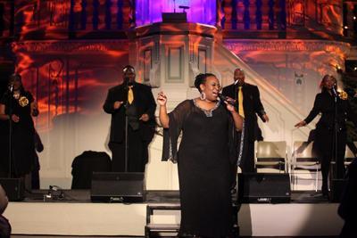 Soulartist Ingrid Arthur iført vakker svart kjole holder mikrofon i venstre hånd og synger. Fire musikere står i bakgrunnen.