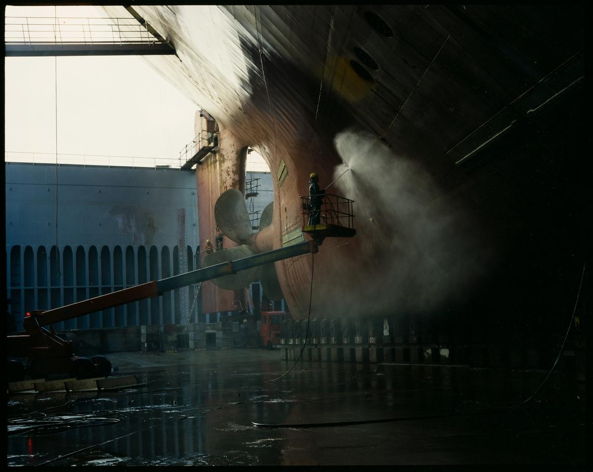 """Høytrykkspyling av kjølen på """"M/S Taiko"""" (Wilhelmsen) i tørrdokken til Haugesund Mekaniske Verksted."""