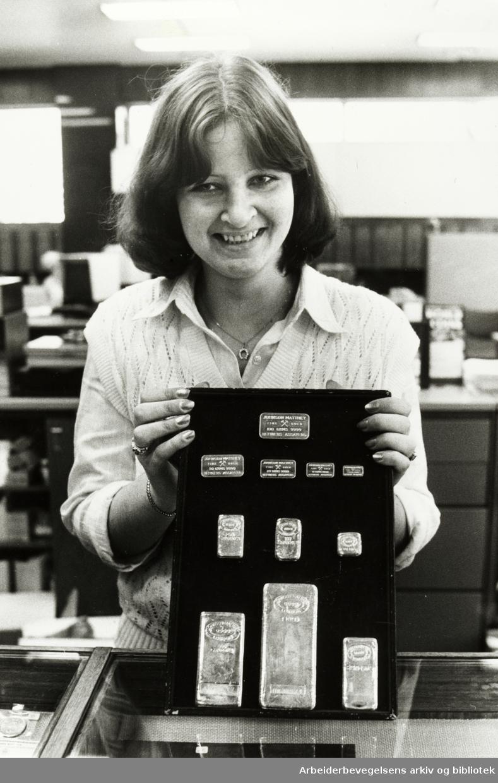 Kredittkassen på Stortorget. En av bankassistentene viser frem gullbarrer i forskjelllige størrelser. Mai 1979