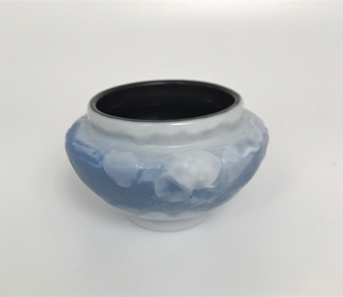 """Skål i overfangglass. Glassmassen består av tre lag, hvorav det innerste laget er dypt rødlig, det mellomste er himmelblått, og det ytterste er melkehvitt. Det ytre laget er delvis skåret bort slik at den blå massen tidvis skinner igjennom.  Det hvite laget danner buktende blader og grener i lavt relieff. På den blå bunnen er følgende innskrifter utskåret: """"vobis facile non deficientem în coelis thesavivm"""" (lat. det er lett for dere ikke å mangle skatter i himmelen)  og """"Gallé 1900""""."""