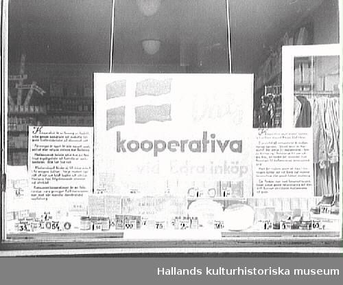 """Skyltfönster till Kooperativa AB, butik i Varberg. """"Välj kooperativa vid Edra inköp"""" står det på en stor skylt i fönstret. I bakgrunden syns en stång med kläder."""