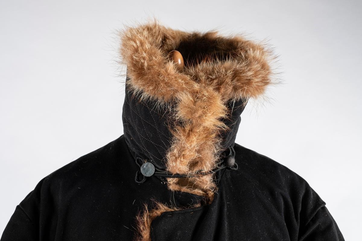 Frakk av bomull med pelsforing. Den har en bred krage. Kragen og mansjettene er kledd med pels. Frakken kneppes i halsen med knapp og hempe på hver side. Ved nedre kant er det brodert 3 røde kryss.