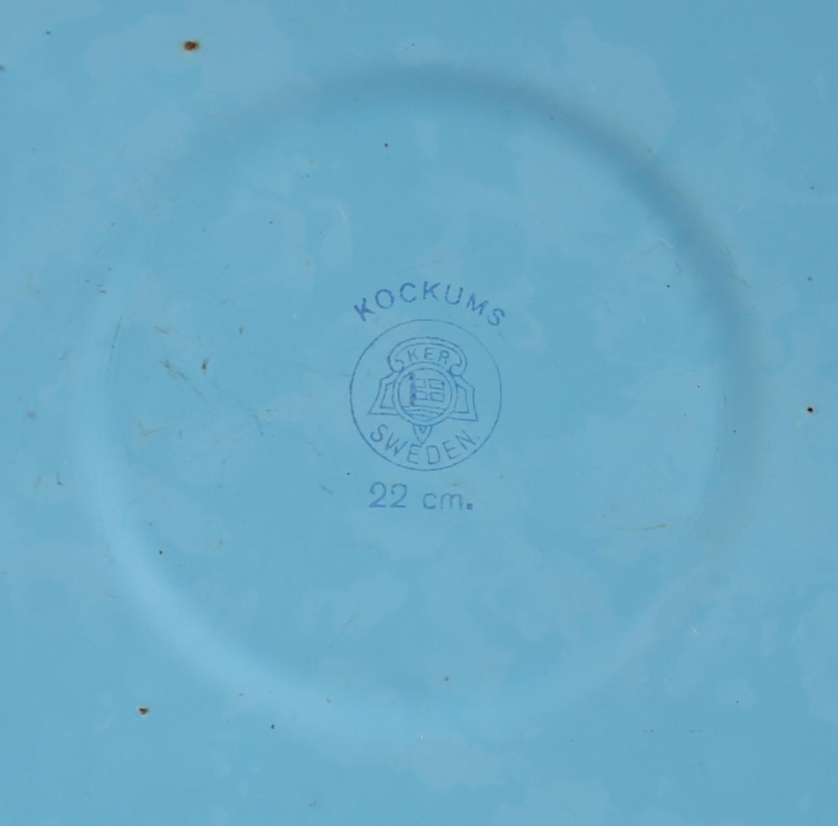Sylindrisk forma kasserolle/gryte. Kasserollen har tynn botn og avrunda munningsrand. På øvste del av kasserollen to handtak støypt i eitt med korpus. Kasserollen er emaljert innvendig og utvendig i to ulike fargar. Tilhøyrande lokk er sirkelrundt med svak kvelving opp mot toppen der det er eit handtak midt på. Ytst har lokket flat kant for anlegg mot munningsranda på kasserollen. Emaljert inn- og utvendig.