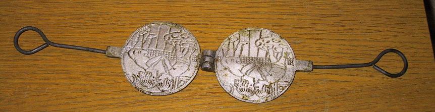 Kakejern av metall med mønster innvendig; to barn, gutt og pike