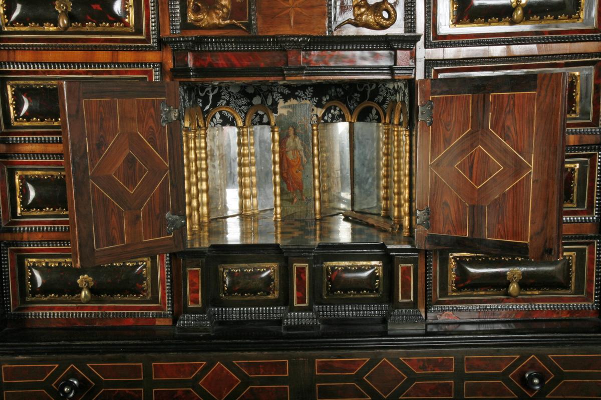 Skapet er en norditaliensk kabinettype på fire dreiede balustre. Fotplate ny og øvre avslutning sannsynligvis endret.  Skilpadde-innlegninger, dør med speilrom på midten med fillete, sekundær tapet.
