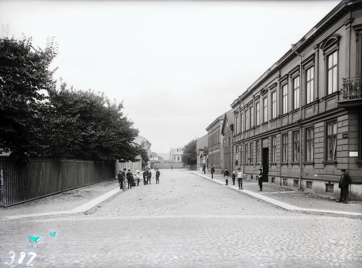 """Skolgatan mot öster från Kapellgatan i Jönköping, innan Skolgatan lagts ut i sin hela längd 1918. Till vänster syns den obebyggda tomten med adress Västra Storgatan 25. Gatan blockerades av """"Lilla Trädgård"""". Flera av byggnaderna finns ännu kvar år 2004."""