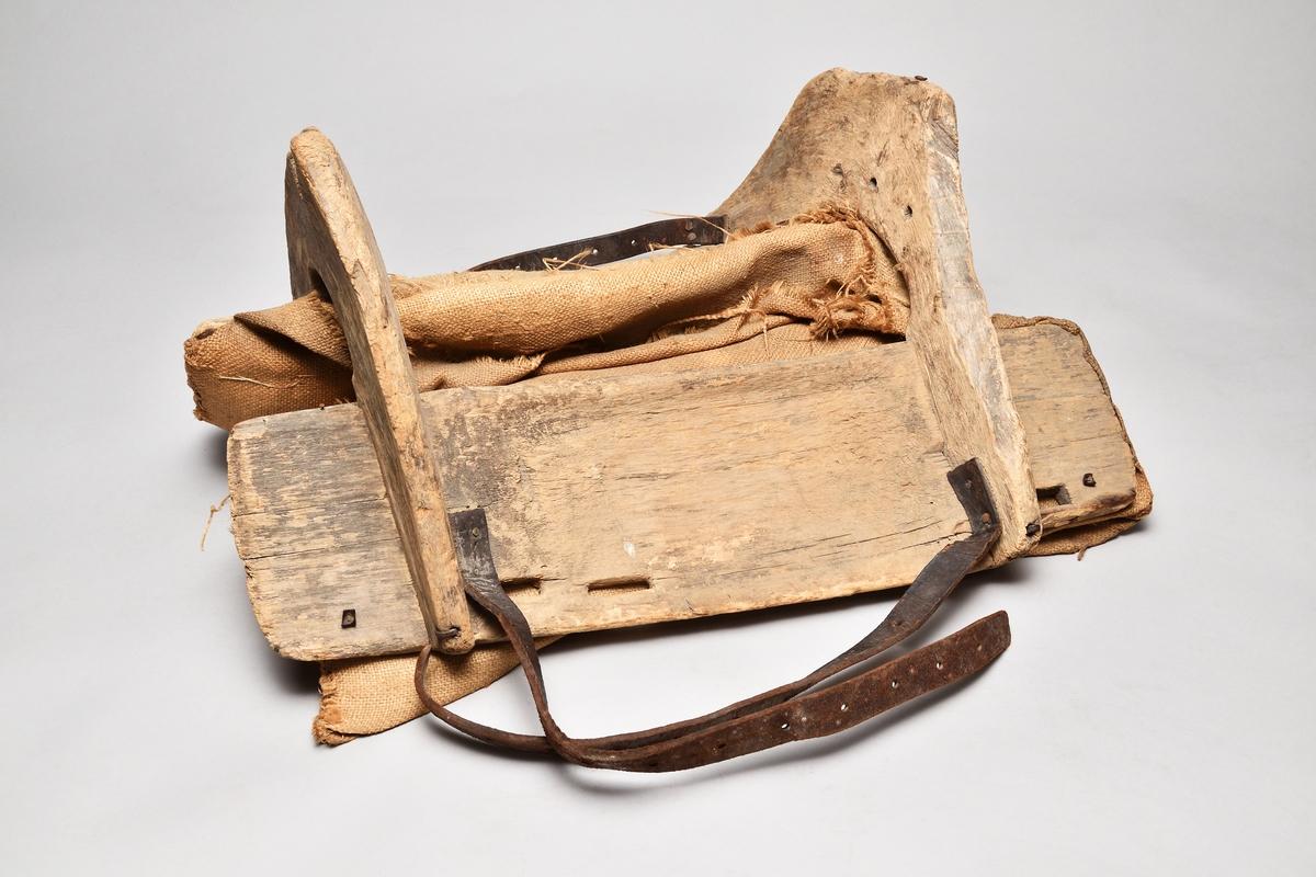 Klövjsadel med sido- och tvärstycken av trä. Mittdelen består av säckväv, stoppad med krollsplint. Båda tvärstyckena (eller valven) har en toppig form, det bakre är avhugget och det främre har ett v-format urtag. Nertill på tvärstyckena finns avlånga hål, troligen för remmar. Fyra korta spännremmar finns fortfarande kvar på sadeln. I bakre tvärstycket finns två hål där det troligen suttit en bygel.