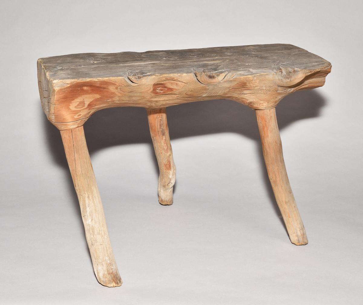 Pall av trä. Gjort i ett självvuxet stycke där de tre benen utgörs av grenarna. Rektangulär sits.