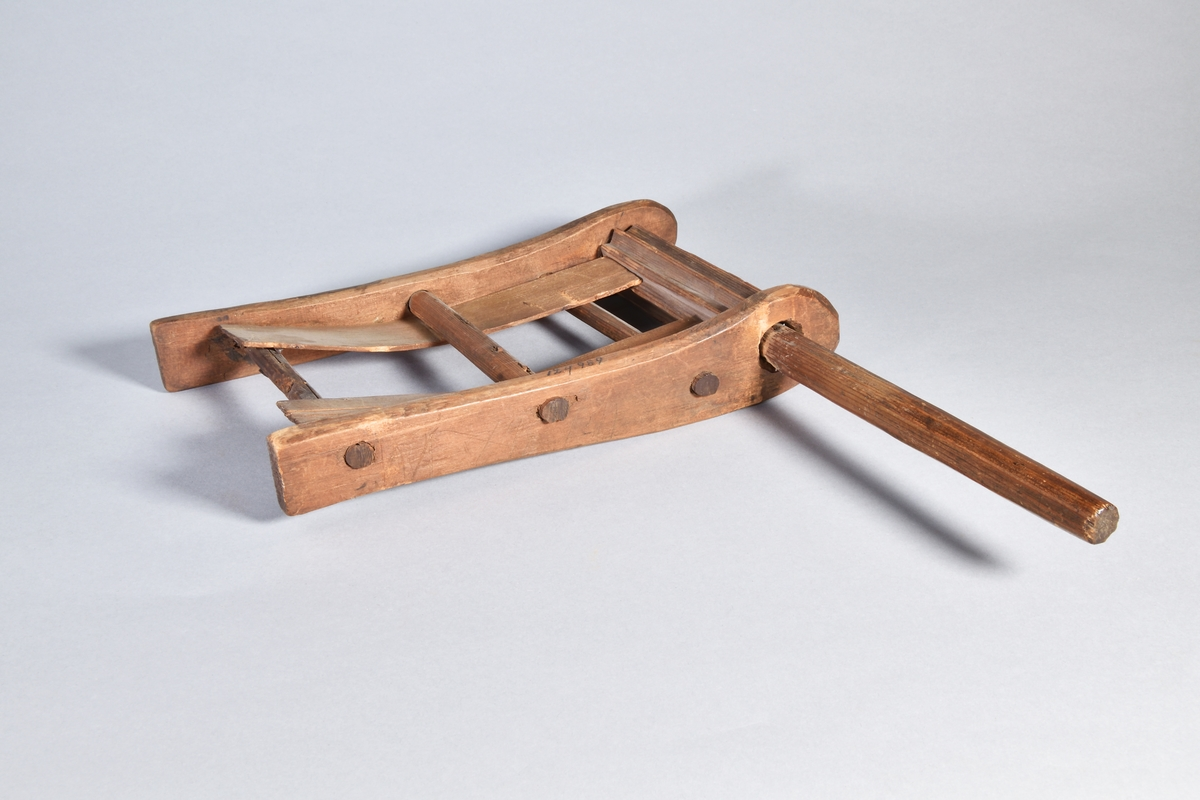 Harskramla av omålad furu. Ram, rektangulär, med rundade sidoskalmar, i ena ändan en vals med åtta valkar samt handtag. Två bitar furuspån löpandes i ramen för att mot valsen framkalla läten.