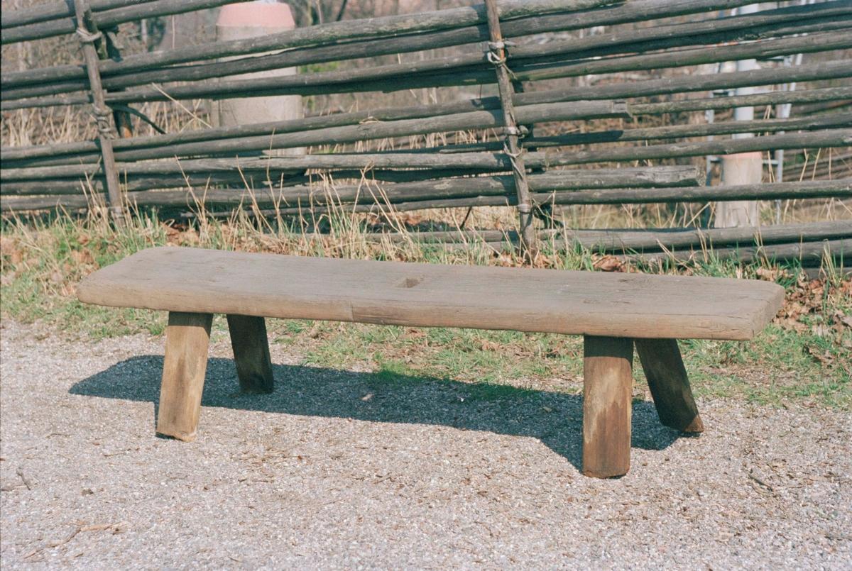 Bänk av furu. Plan sittbräda, fyra itappade platta ben, något utställda. Fyrkantigt uttag mitt på sittbrädan. Följde med eldhuset till Skansen.