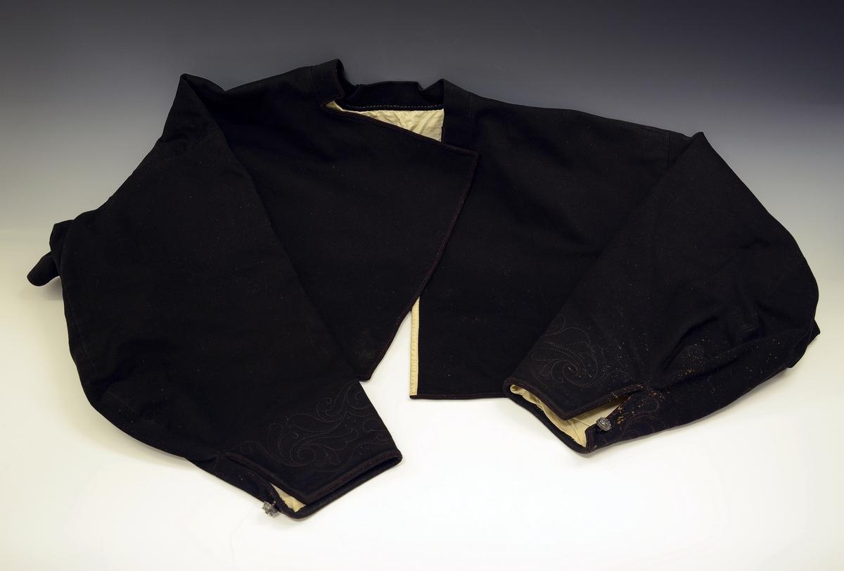 Består av: I: Slengtrøye av svart klæde, nyare type, sidare og meir stikka.  Kvinnetrøye av svart vadmel. Burgunder tittekant langs kragen, framslaget, nedrekanten og rundt ermene. Under slaget er det 2 metallhekter.   Rundt ermene nederst er det hånsydde stikninger. Innvendig er trøyen fòret med hvitt bomullstøy.