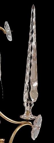 Ljuskrona med stomme uppbyggd av volutformade brännförgyllda mässningsstavar. Upptill en plymliknande konstruktion dekorerad med lövformade slipade prismor och gjutna margueriter. Ljuskronans stomme har sex ljusarmar fästa i en järnplatta med täckbricka av förgylld mässingsplåt. Ljusarmen avslutas med gjutna ljuspipor och droppskålar. Mittstång av järn med blåst stamglas format som ett slipat klot upptilll krönt med en obelisk. Ljusarmarna är dekorerade med lövformade slipade prismor och gjutna margueriter. Till varje ljusarm finns sex obelisker med slipade ytterkanter. Stommen är dekorerad med stavverk av glasrör och glaspärlor trädda på metalltråd. Nedtill hänger ett större glasklot med slipad dekor.