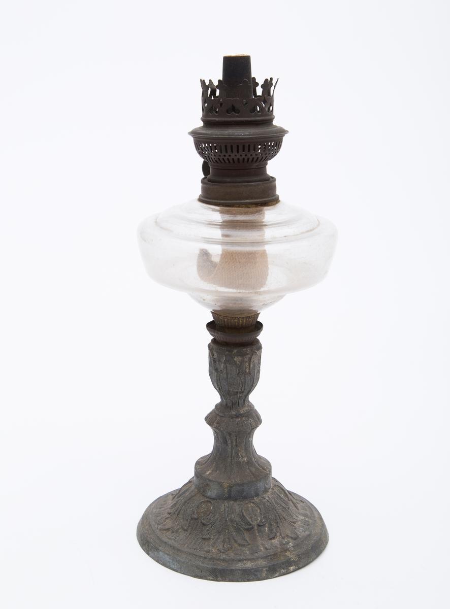 Sirkelrund fot med søyle. Parafinbeholder i glass. Veke. Stilistisk bladranke til pynt. Lampeglass og skjerm mangler
