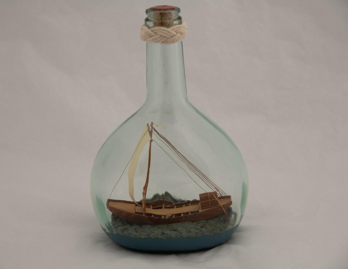 Flaskeskute: Egyptisk fartøy 1565-1080 f. Kr.  Flaske av klart glass (likørflaske) , innst. i bunnen 380 og g F. Oval bunn , flat på to sider , skrå skuldre , hals med en knop i seilgarn , munningen tettet med rød lakk. Bredbunnet skip , flatbunnet med trekantet seil , to styreårer bak og kahytt akter.