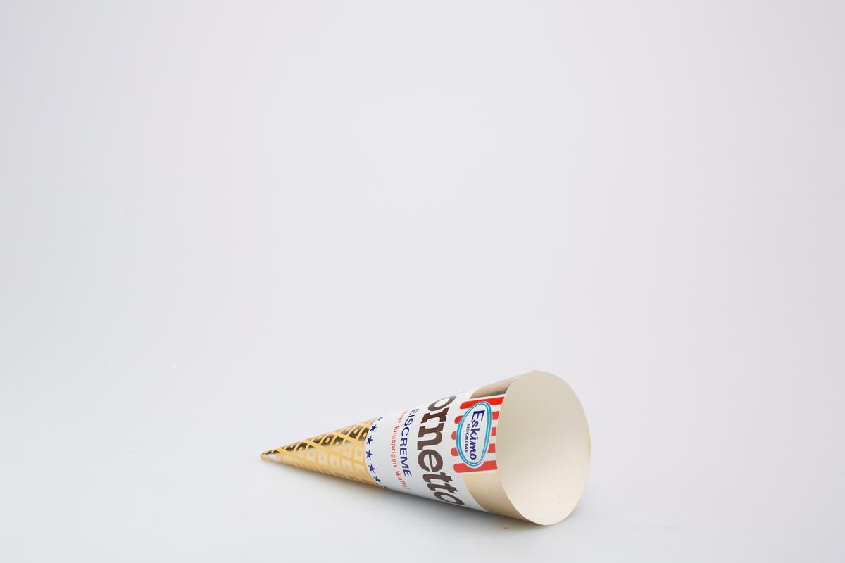 Kjegleformet iskrempapir (kremmerhus) i aluminium og papir. Kremmerhuset er med farger på utsiden, og uten farge (hvit) på innsiden. Kremmerhuset har gull bakgrunnsfarge med hvitt felt med tekster i midten og felt med rutete mønster nederst.