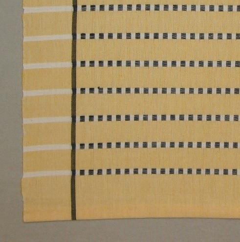 """Randig duk, tre stycken, vävd i tuskaft med ränder i inslagsflottering av tvåtrådigt bomullsgarn. En duk är blågrön (turkos) en rosa och en gul. Varpen är blekt med en smal svart rand i varje sida 45 mm in från kanten. Tuskaftsinslaget är färgat med blekta smala ränder med svarta flotteringar. De färgade tuskaftsränderna är 20 mm breda och de blekta 5 mm. De svarta flotteringarna bildar rutor  på de blekta ränderna, men är vävda endast mellan de svarta ränderna i varpen, vilket ger endast blekta ränder i sidan. Alla tre dukarna har smala tråcklade fållar.Den första duken är blågrön (turkos) och är märkt med R7:1 på ett vitt bomullsband. I ena hörnet är en pappersetikett fastsatt med häftklammer. Texten lyder: """"DUK FLOTT BOMULL MODELL"""". En gul prick med ett S är klistrat på etiketten. På andra sidan av etiketten är det en tryckt spånfågel med texten """"LÄNSHEMSLÖJDEN SKARABORG SKÖVDE - LIDKÖPING"""".Den andra duken är rosa och är märkt med R7:2 på ett vitt bomullsband. I ena hörnet är en pappersetikett fastsatt med häftklammer. Texten lyder: """"DUK FLOTT BOMULL MODELL"""".På andra sidan av etiketten är det en tryckt spånfågel med texten """"LÄNSHEMSLÖJDEN SKARABORG"""".Den tredje duken är gul och är märkt med R7:3 på ett vitt bomullsband. I två av hörnen är pappersetiketter fastsatta med häftklammer. På den ena lyder texten: """"DUK FLOTT BOMULL TVÄTT 60 90 X 90 S 290:-"""". På andra sidan av etiketten är det en tryckt spånfågel med texten Länshemslöjden Skaraborg. På den andra etiketten lyder texten: Duk FLOTT Bomull, Ann-Mari Nilsson, tvätt 60, S 298:-.  På andra sidan av etiketten är det en tryckt spånfågel med texten Länshemslöjden SKARABORG SKÖVDE"""".Duken med modellnamnet Flott är formgiven av Ann-Mari Nilsson och tillverkad av Länshemslöjden Skaraborg. Den finns med  på sidan 22-23 i vävboken Inredningsvävar av Ann-Mari Nilsson i samarbete med Länshemslöjden Skaraborg från 1987, ICA Bokförlag. Se även inv.nr. 1-6,8-40."""