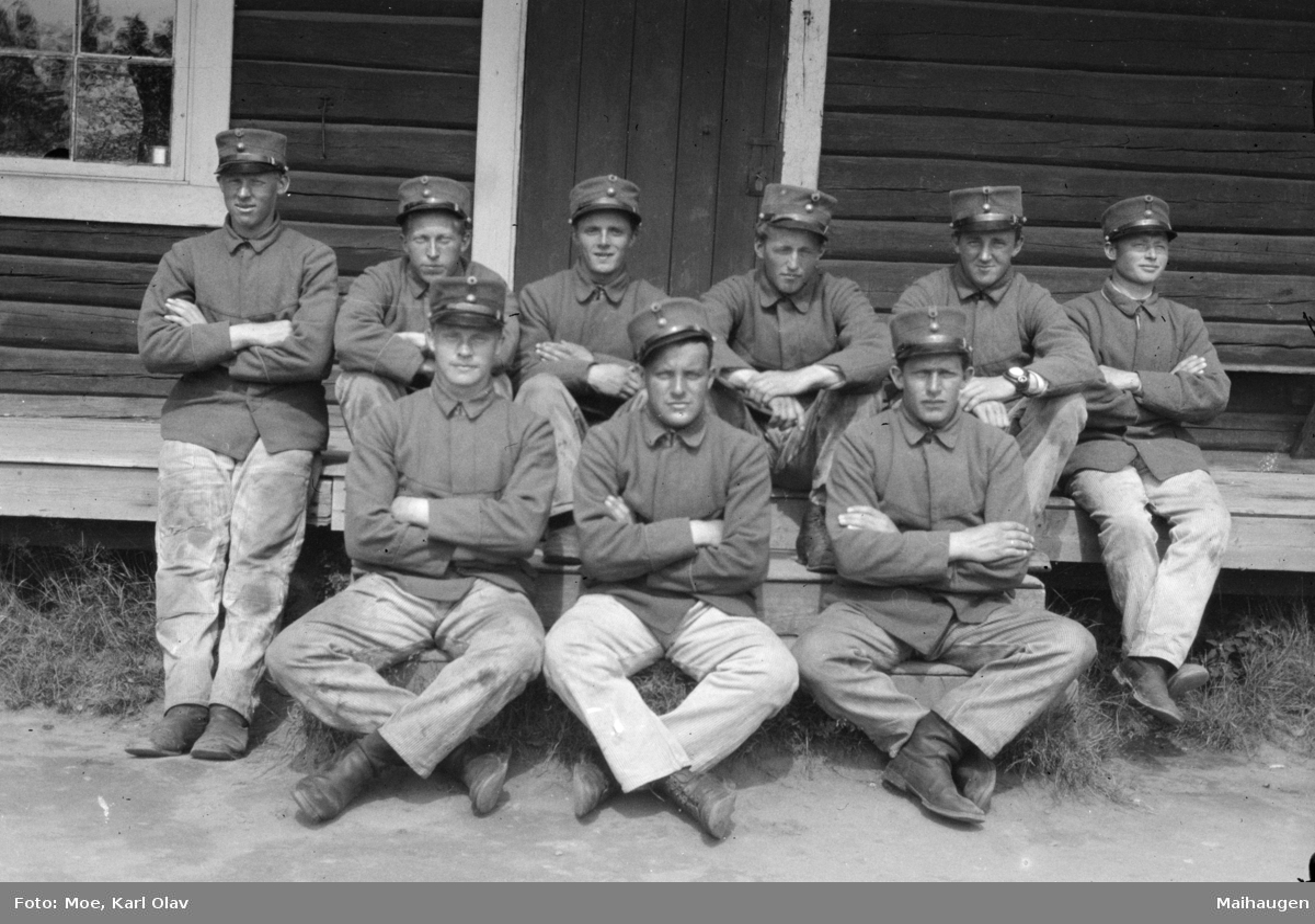 Ti soldater poserer på ei trapp utenfor en tømmerbygning.