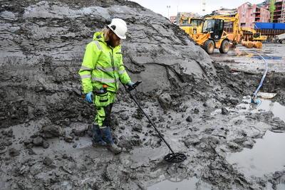 Arkeolog Lars Bigum Kvernberg med metalldetektor nede i sjøbunnsleira på B8a