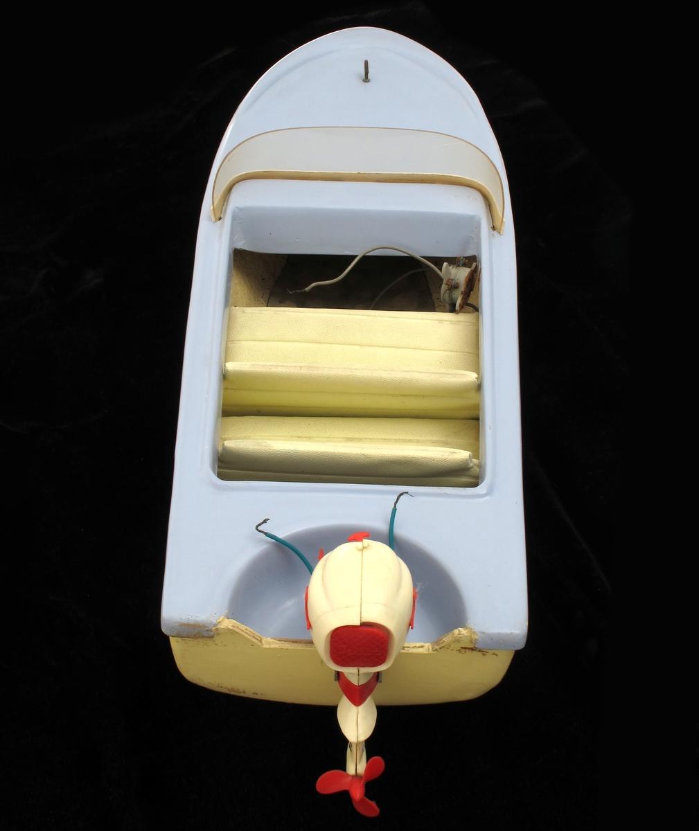 Lekemotorbåt, helt i plast, noe kryssfiner, med påhengsmotor. Batteridrevet. Skroget er gul farge, dekket er lys blå.