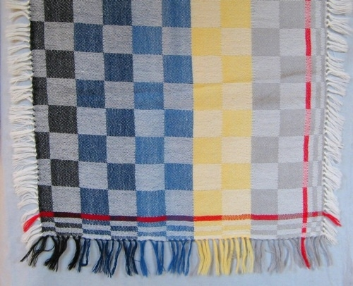 Rutigt vävprov till schal vävt i 10skafts dräll med kypert som grundbindning. Varp och inslag är tunt tvåtrådigt ullgarn. Varpen är naturvit och inslaget ljust grått, gult, blått, mörkblått och svart. Vävprovet är schackrutigt med två rutrader av varje inslagsfärg. Det är fem rader med smala rutor längs tre av ytterkanterna. Den femte rutranden är röd i både varp och inslagsriktning. Det är frans runt hela vävprovet knuten med pärlknut.  Vävprovet är formgivet av Ann-Mari Nilsson. Se även inv.nr.0120 Schal.