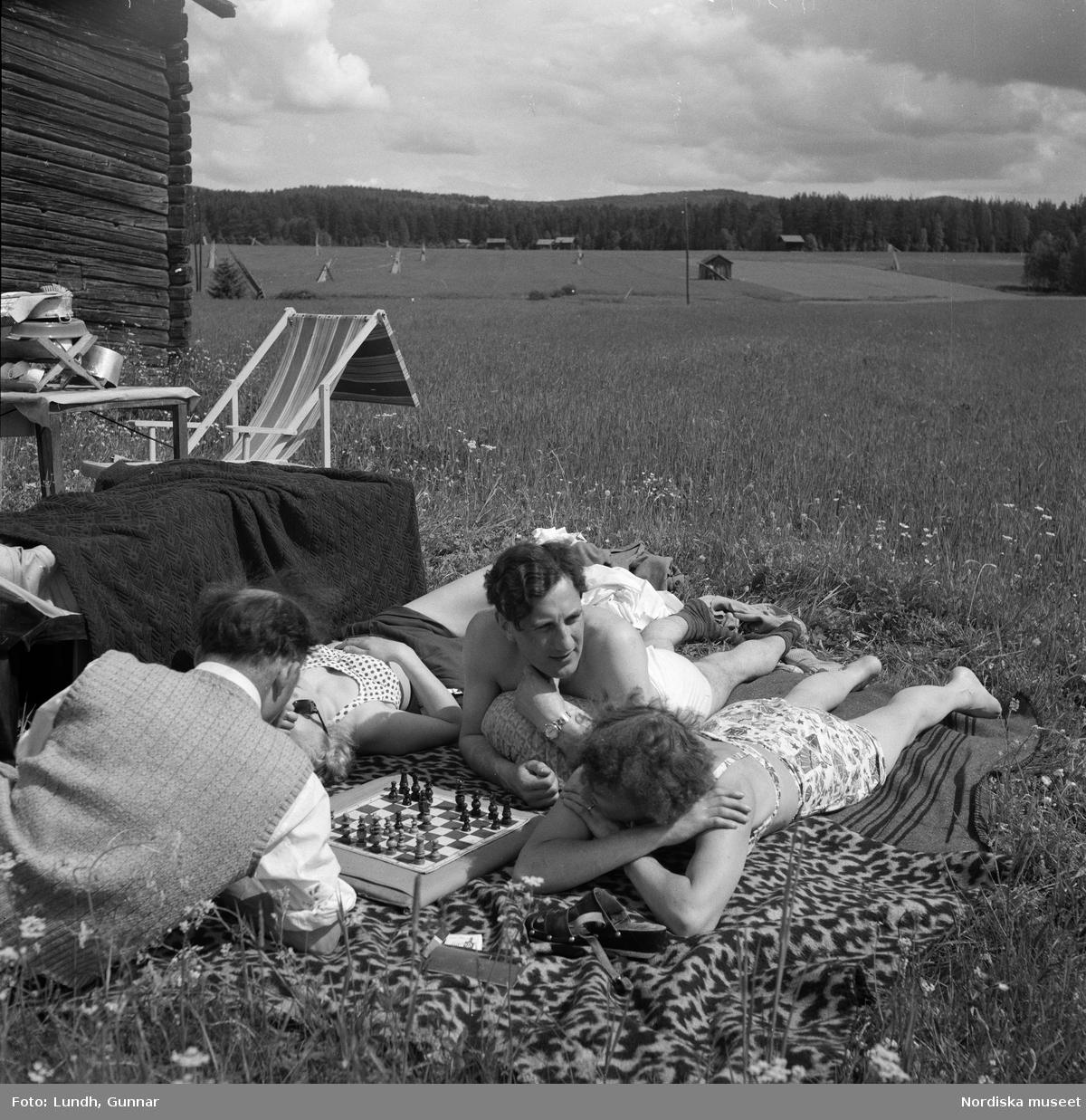 Motiv: (ingen anteckning) ; Porträtt av en man författaren Frans G Bengtsson, en gärsgård, två kvinnor och två män ligger på marken och spelar schack vid en parkerad bil med husvagn, en kvinna står vid dörren till en husvagn, porträtt av en flicka som håller blommor.