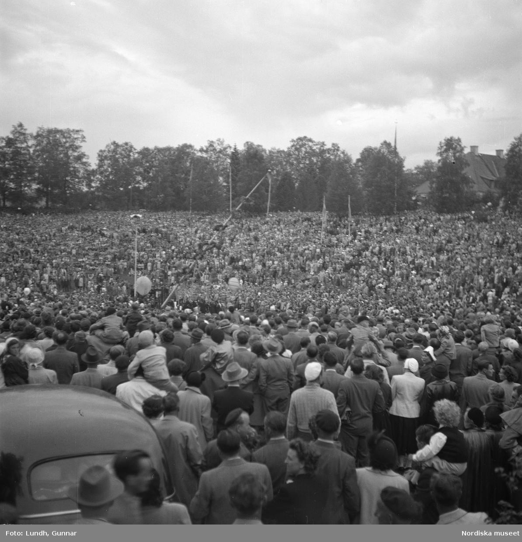 """Motiv: (ingen anteckning) ; Två kvinnor och en man i folkdräkt bär ett lövat hjärta, män i folkdräkt spelar fiol, en folksamling tittar på ett midsommartåg genom ett samhälle, en folksamling """"S????dal Leksand""""."""