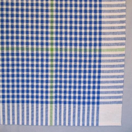 """Smårutig duk vävd i tuskaft av cottolin i blekt och blått med en effektrand i grönt. Runt kanten är det ett enfärgat blekt parti 95 mm brett.  Den gröna effektranden är 300 mm in från kanten i ena sidan. Den gröna effektranden i både varp och inslag gör att duken får två olika motstående hörn. Duken har en smal tråcklad fåll i två sidor.  I ett av hörnen är en pappersetikett fastsatt med häftklammer. Texten lyder: """"Cottolin Ann-Marie Nilsson 398:-"""". På andra sidan av etiketten är det en tryckt spånfågel med texten """"LÄNSHEMSLÖJDEN SKARABORG"""".   Duken med modellnamnet Blockruta är formgiven av Ann-Mari Nilsson och tillverkad av Länshemslöjden Skaraborg. Se även inv.nr. 0147 Duk i annan färgställning."""