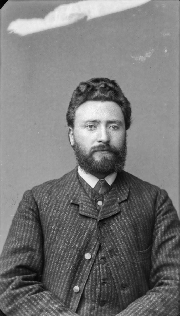Portrett av mann med mørkt hår, bart og sjegg, kledd i kvit sjorte, slips og stripet vest og jakke