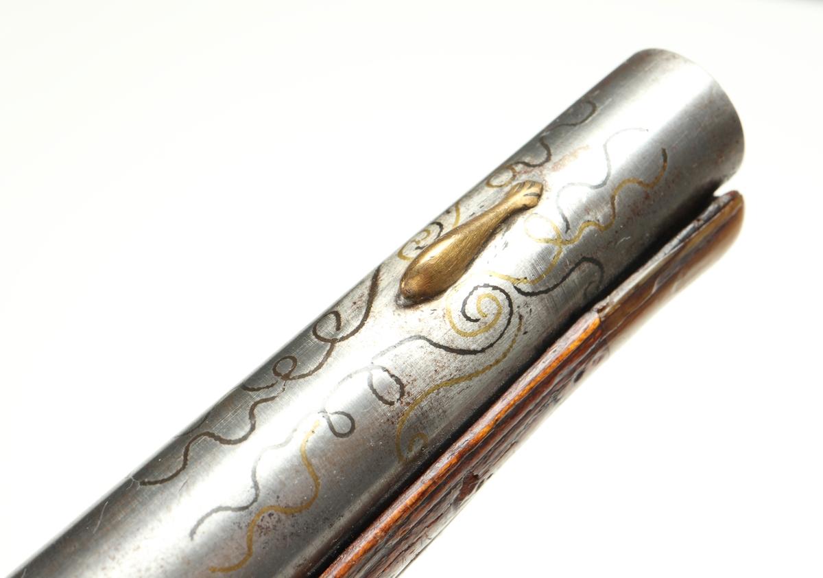 Slaglåspistol omändrad från flintlås. Den har helstock med några få utskärningar. Kolvkappa, sidobleck, låsbleck, rörkor, hane och varbygel samt pipa tillverkade i polerat stål försett med ciselerade blomsterdetaljer. Pipan har även inläggningar i mässing baktill samt runt kornet. Pistolen har ett filat gropsikte, och det finns ett korn av mässing. Mynningsblecket samt stötändan på laddstocken har hornbeslag. Pipan är slätborrad med en innerdiameter på 13 mm.  Inskrivet i huvudkatalog 1890.