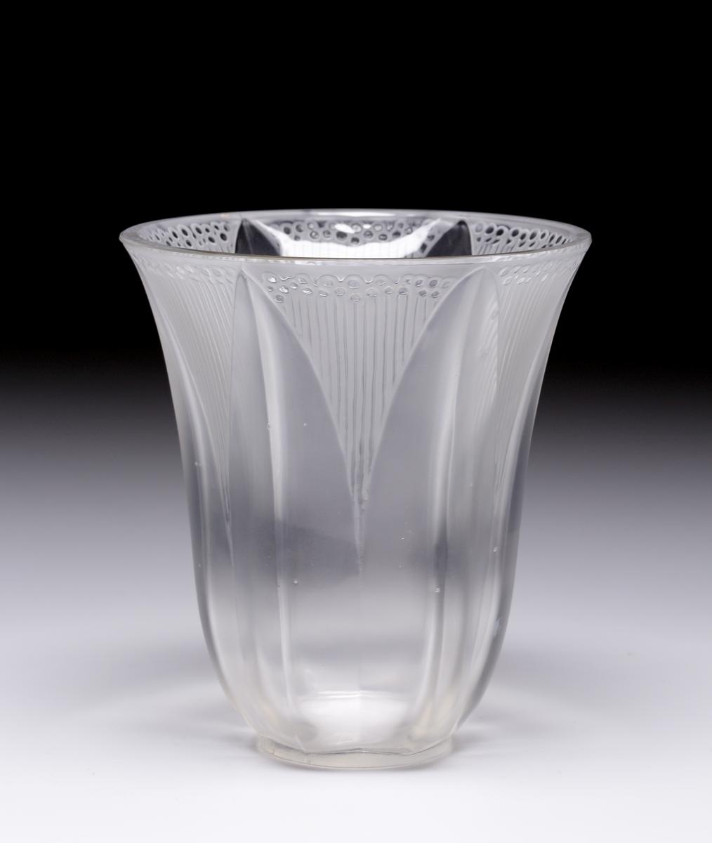 """Vas i ofärgat glas med olika matthet. Mönster med spetsbågar, refflor och små ringar. Enligt registerkortet fanns tidigare en etikett: Prislapp från Svenskt Tenn """"E 815 25 kr"""""""