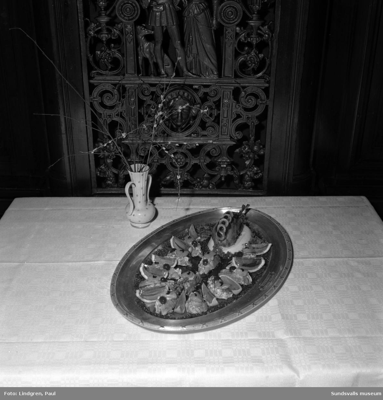 """Uppläggningsfat med """"Kall järpe à la Carmen"""". Köksmästare Alois Ebnöther på Knaust hotell beskriver den delikata rätten som tips till läsarna i ett reportage i ST. Fåglarna steks och fylls med gåsleverpastej samt garneras med ananas och körsbär samt övergjuts med madeiragelé. Klyftor av apelsinskal med rosafärgad apelsingelé mellan fågelfiléerna.  Rätten serveras med pariserpotatis och fruktsallad med majonäs."""