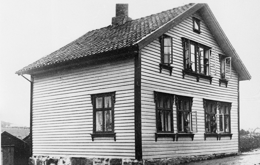 Storgata 31, Bryne. Huset var først bygd som smie i 1882, ombygd tilvåninghus i 1890. Kåre Holen er eigar frå 1950. I vinauga i 1. etg. f. v. Helena Line Norheim, Gabriel Sivert Norheim, Gunvor Norheim.