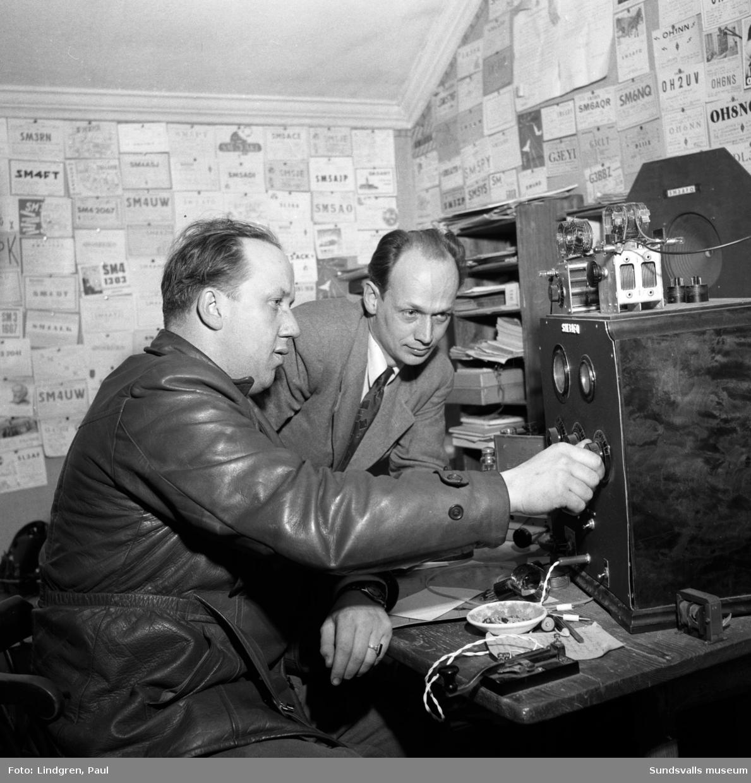 """""""Jakten efter Black Peter"""". Från reportage om radioamatörer. På bilden ses Stig Törnqvist, Kvissleby, och Gunnar Mejerby, Alnö, lyssna till """"Black Peter"""" från Sollefteå. Den anonyme """"Black Peter"""" sade sig sända på 155 watts effekt med hjälp av ett stuprör men med en förstklassig mottagningsapparat."""