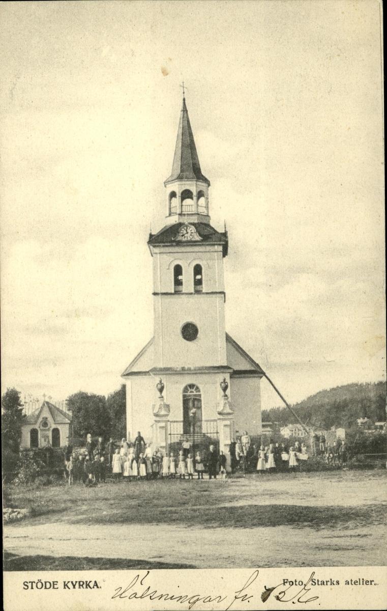 Vykort med motiv av kyrkan i Stöde med en grupp människor uppställda för fotografering utanför.