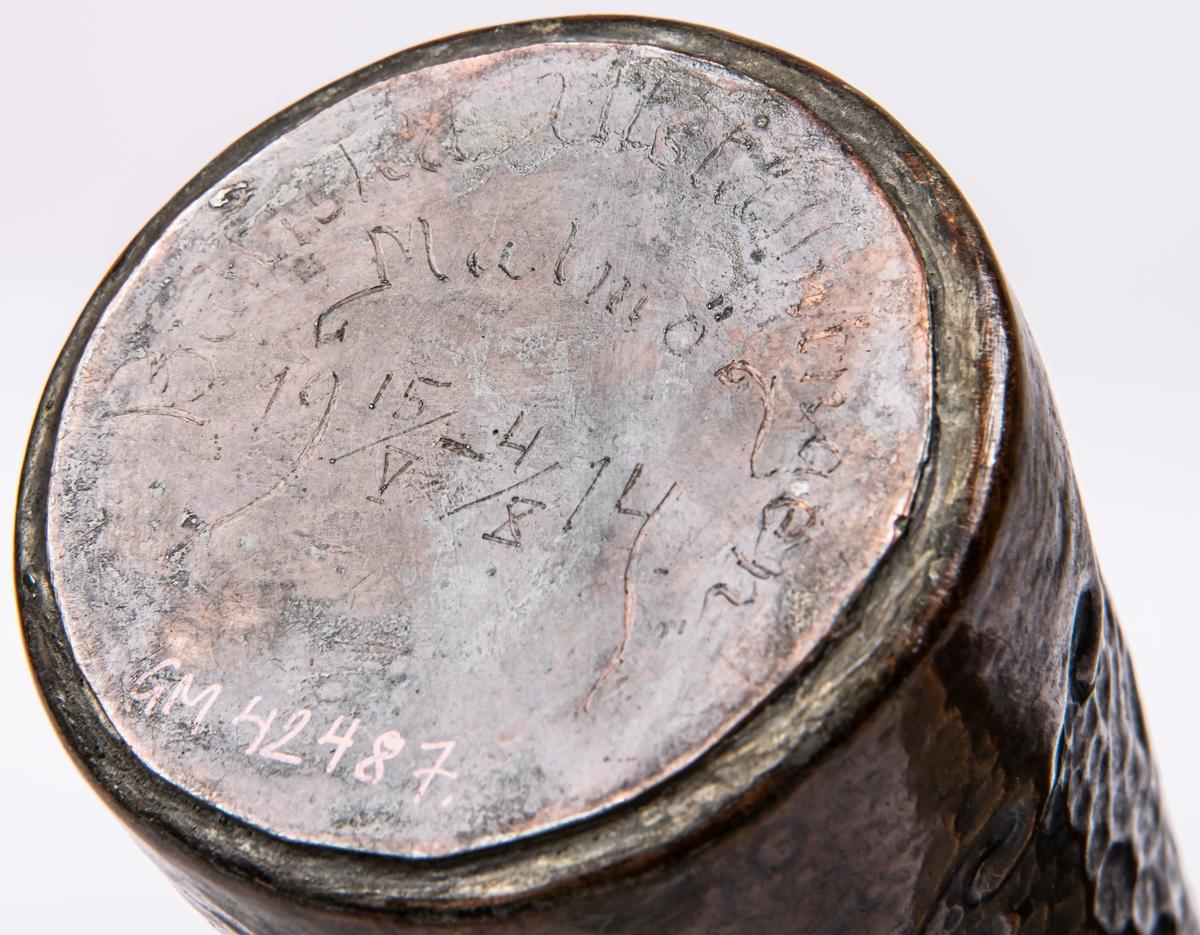 Vas av kopparplåt, föreställande flygande storkar. Undertill märkt: Baltiska utställningen Malmö 14/V-4/X 1914.