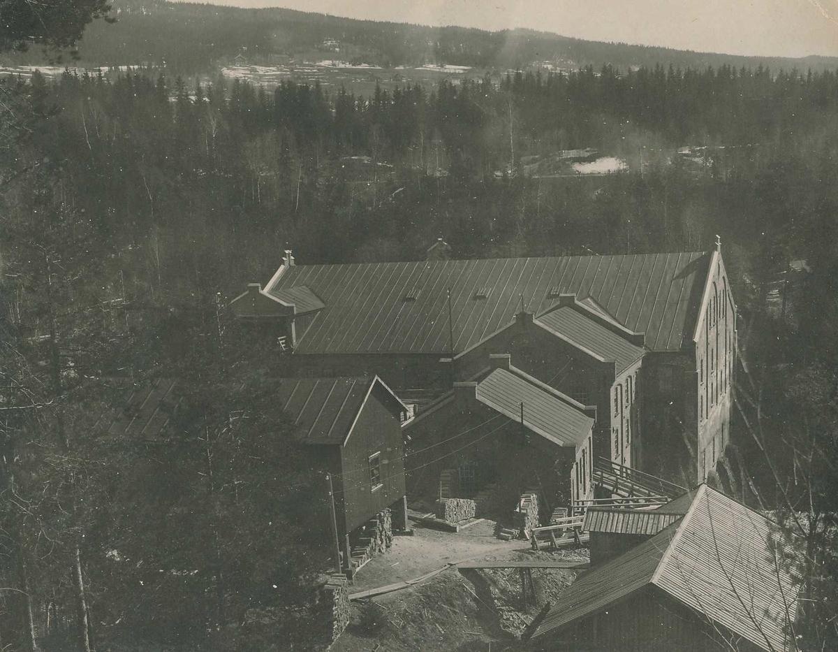 Industrianlegg med bygninger av tegl og tre på A/S Kistefos Træsliberi. Skog, dyrket mark og jernbanetrasé i bakgrunnen.