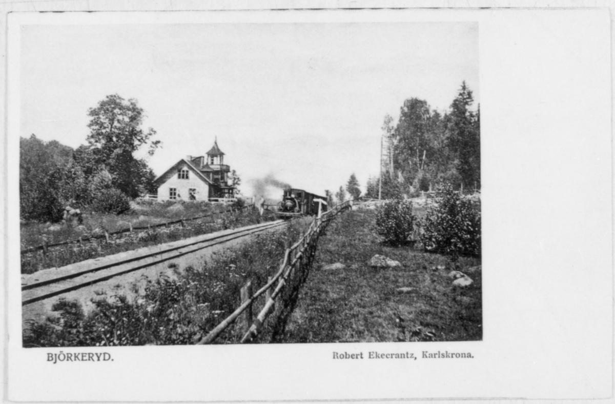 Ångtåg på väg norrut på linjen bredvid en spektakulär byggnad vid Bränteknuvavägen strax söder om Björkeryd.