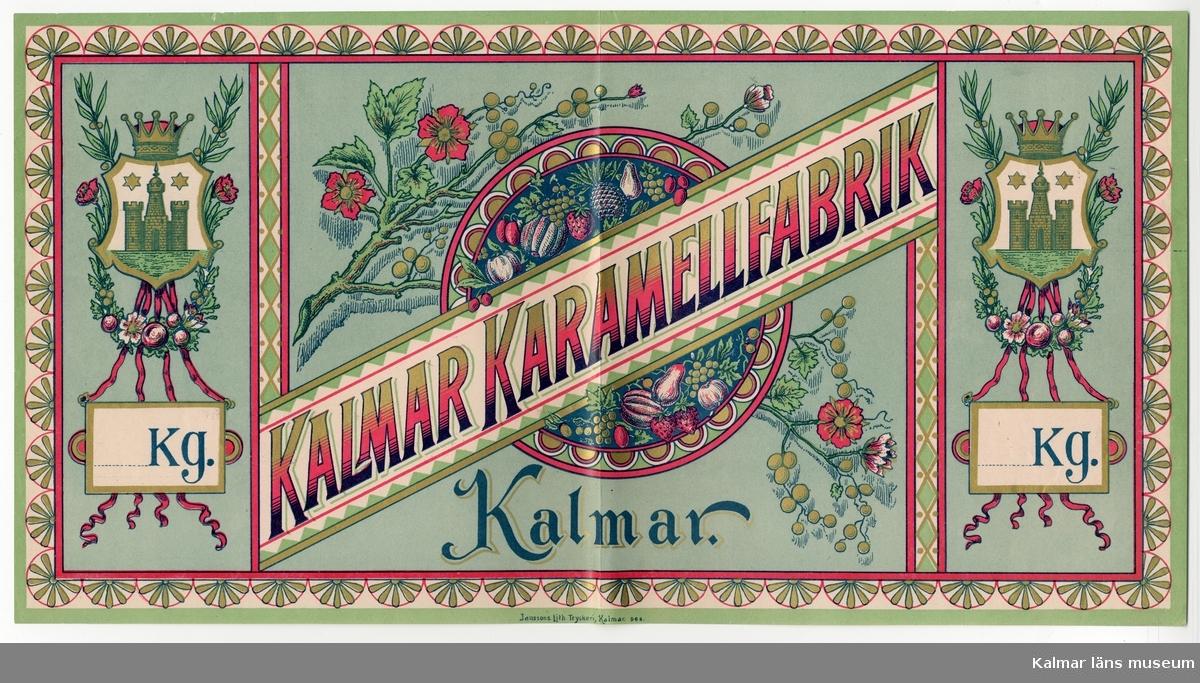 KLM 21360:3:10 Etikett, av papper, tryck av litografisk etikett. På etiketten text, Kalmar karamellfabrik, samt Kalmar stadsvapen. I färgen rosa, guld och vitt på grön bakgrund. Etikett till karamellförpackning. Beställare, Kalmar karamellfabrik, Kalmar. Tryckt på Janssons Litografisk tryckeri i Kalmar. Trycket låg löst i provbok med varuetiketter mm, KLM 21360:1.