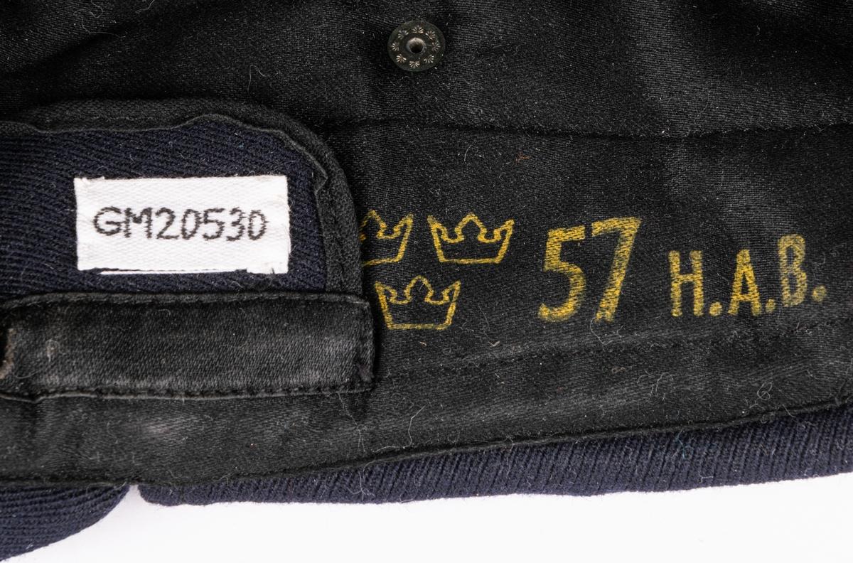 """Vintermössa m/54 med skärm för flygvapnet. Av mörkblå yllegabardin, typ """"skidmössa#. Hög mjuk något oval form med rak mjuk tygskärm. Öronskydd löpande från sidorna bakåt. Nedfällbart pannskydd. Vadderat foder märkt med """"""""tre kronor"""" 57 H.A.B."""" Flygemblem i guldbrodyr framtill."""