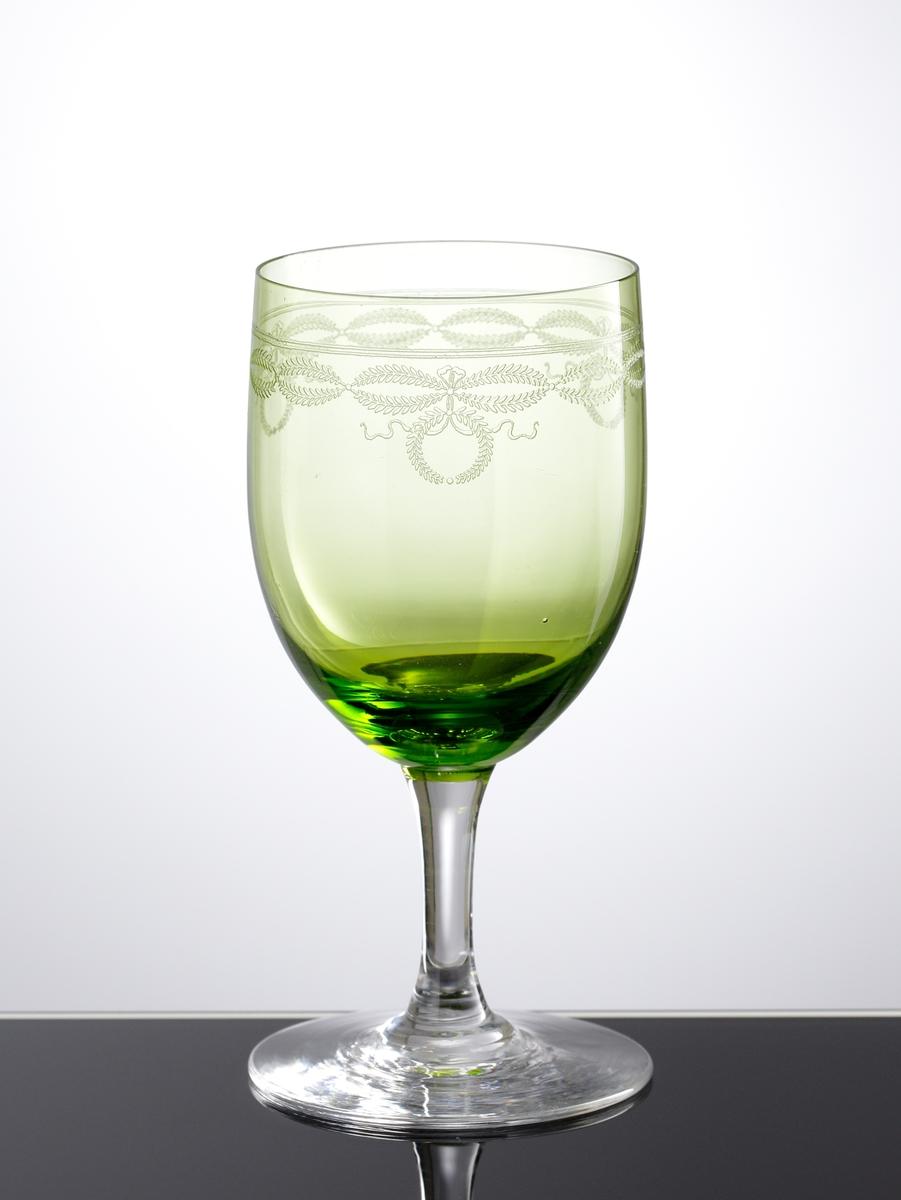 Vinglas i gröntonat klarglas. Pantograferad dekor i form av växtgirlanger och kransar i en bård på kupans övre del.