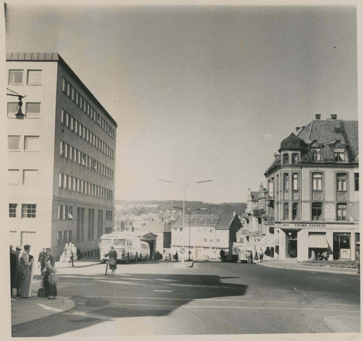 Torggata. Ca. 1960.   Fotograf har stått i Torggata. Detaljer:Dronningens gate 1 til venstre, bybussen og høyvekta, Gudes gate 4. Torvgården til høyre. Historikk: Dronningens gate 1 ble oppført i 1956. Høyvekta ble revet i 1962.