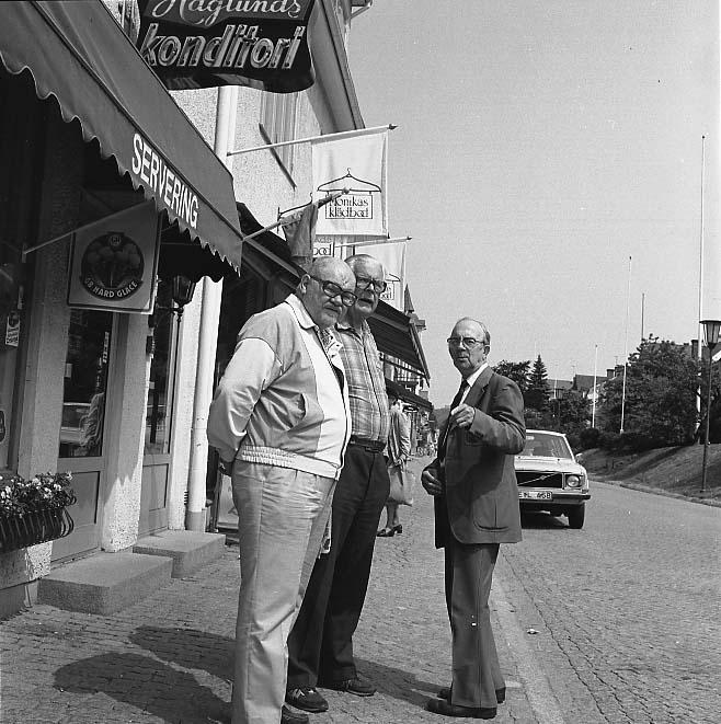Två kraftiga män står på trottoaren utanför Haglunds konditori i Gränna med blicken söderut, en mindre och äldre man står mittemot och pekar söderut. De är sommarklädda. D är från vänster Ragnar Bergelöv och Harry Linder.