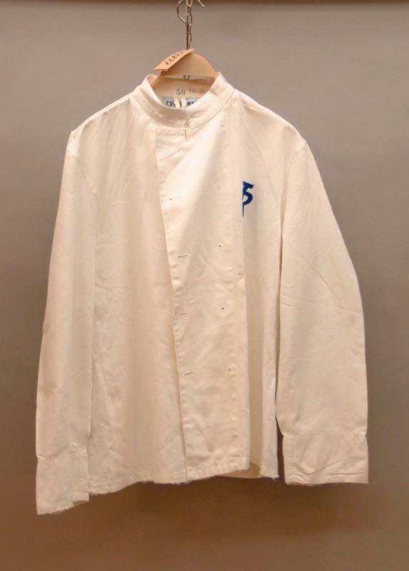 Vit servitörsrock, kort modell. På vänster sida av bröstet finns TR:s logga i blått. Storlek C 58.