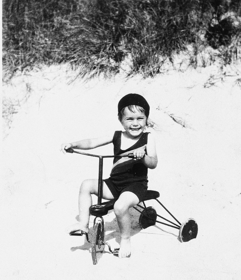 Anne Kristen? Schønborg Darre (Lillemor) på trihjulsykkel i sanden på Orrestranda.