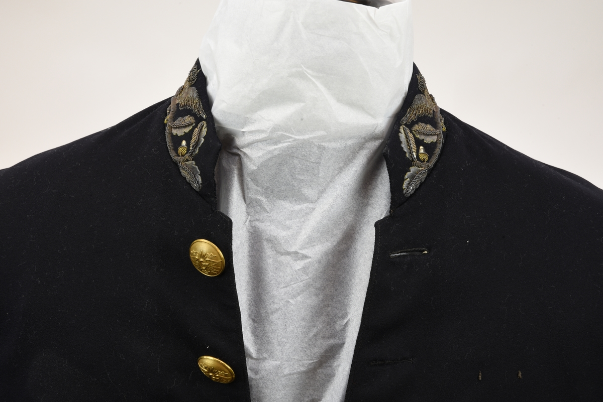 Enkelknäppt paradfrack av mörkblått kläde med liten ståndkrage med metallbroderier i form av vinghjul och enklare eklövsrankor. Fracken har svängd mitt fram-linje och sju guldfärgade knappar.