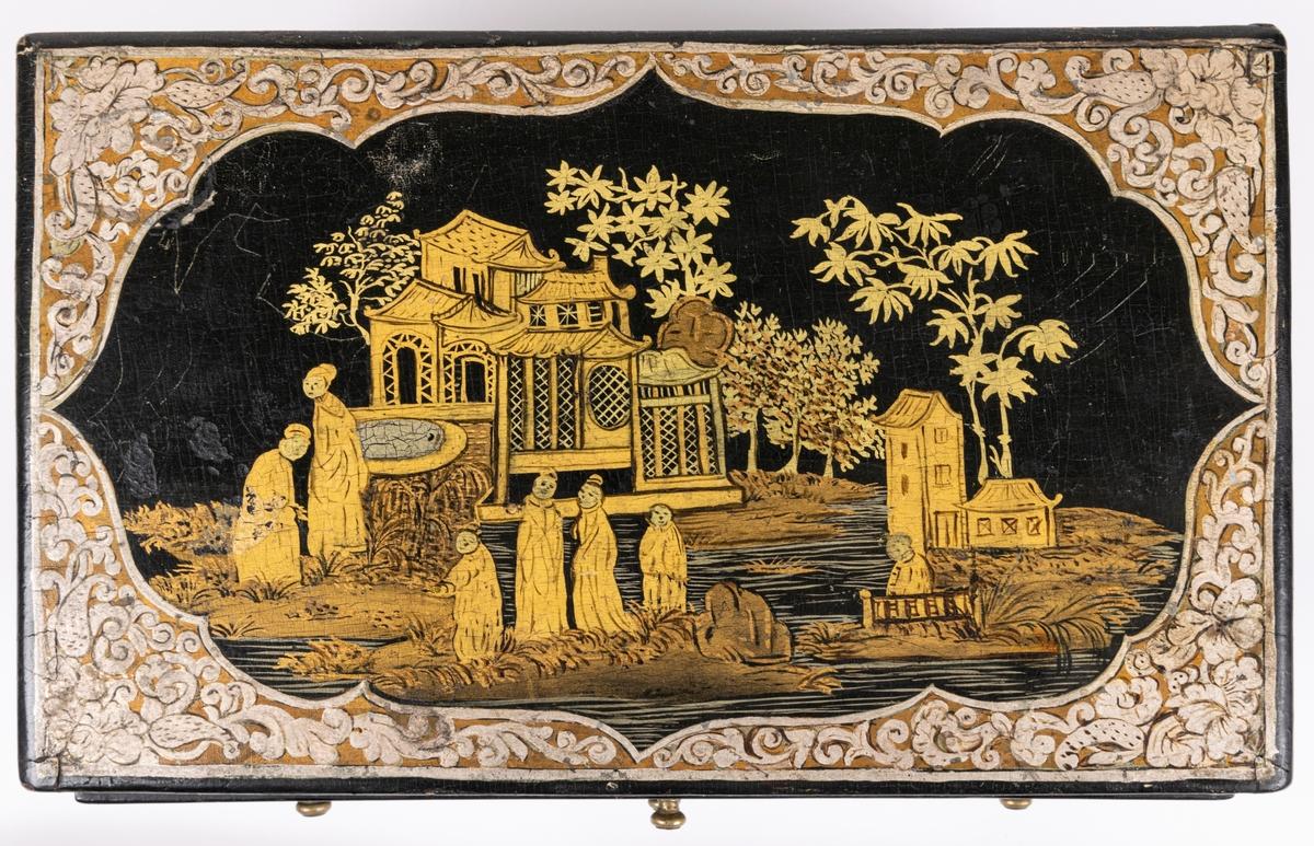 """Kat.kort: Skrin, kinesiskt lackarbete i svart, guld och silver, med landskapsbild och växtornament. Innehåller 9 små lådor, av vilka en är smal, sträckande sig över hela schatullets längd. Några av lådorna äro indelade i fack. Innuti klädda med rödaktig sammet. På undersidan av vänster låda nertill är skrivet """"Philip Berhard Hebbe...1772"""" /el. 1779?/. Gästrikland."""