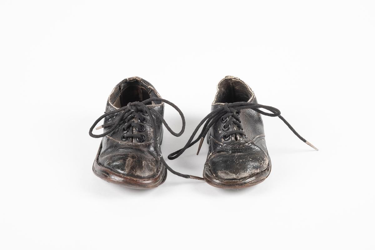 Ett par randsydd barnesko av lær. Skoene har snøring med runde lisser. Maljene er av metall. Sålen er av lær og er forsterket med spiker på hælen og ved tuppen på undersiden.